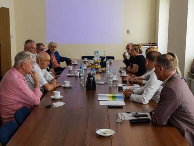 Zdjęcie ze spotkania; osoby rozmawiające przy stole w sali konferencyjnej.