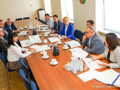Uczestnicy spotkania, zasiadający przy stole.