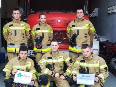 Strażacy z OSP przy wozie strażackim.