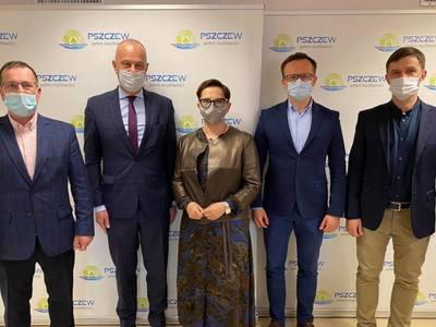 Pięć osób na tle ścianki promocyjnej gminy Pszczew.