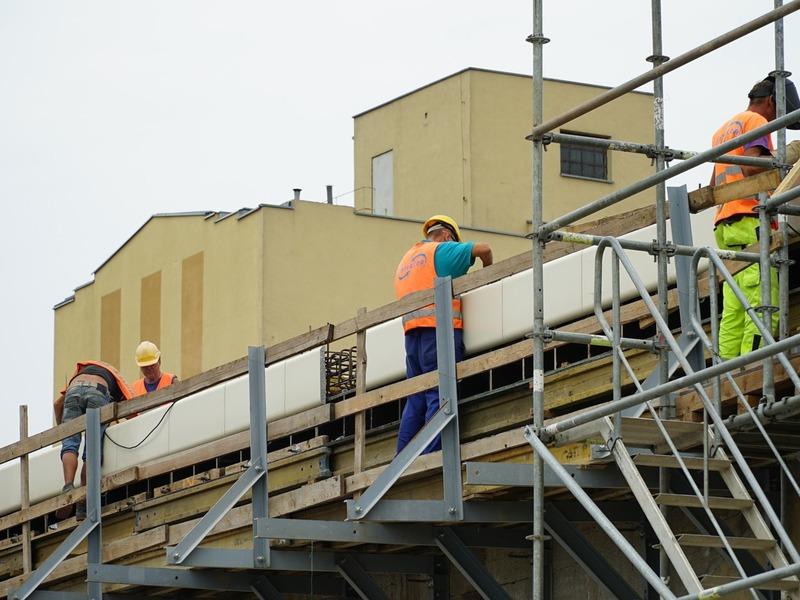 Robotnicy pracujący na rusztowaniu.