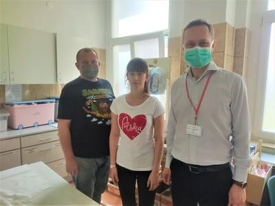 Trzy osoby stojące obok siebie w gabinecie lekarskim.